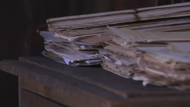 stockvideo's en b-roll-footage met angled cu stacks of yellowed paper folders on dusty wooden table desk - dossier