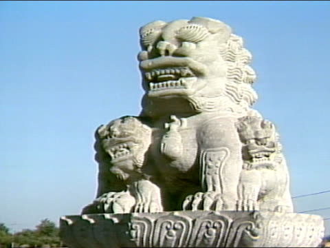 angled ws the lugou bridge w/ large small lion statues lining tops of columns pan lions on bridge to close grouping - stone object stock videos & royalty-free footage