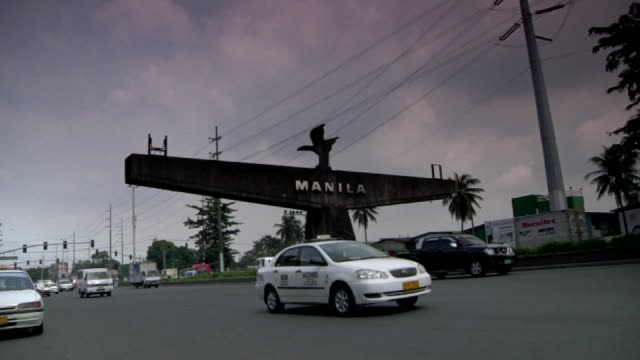 angled ws traffic moving through frame w/ large freestanding manila sign on median bg zi ws manila sign topped w/ statue of bird in flight possibly a... - luzon stock videos & royalty-free footage