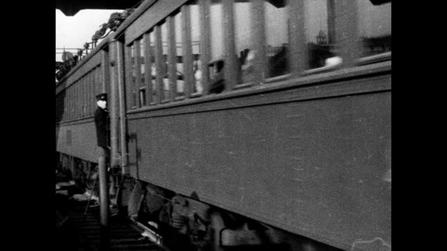 vídeos y material grabado en eventos de stock de angled train moving up tracks w/ conductor standing outside in step well, conductor walking down aisle of commuter train car . - 1934