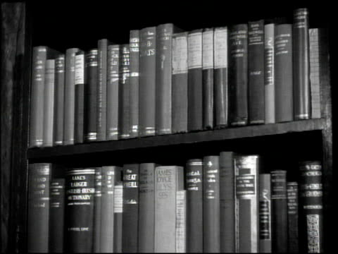 angled ws two bookshelves holding books published by irish authors james joyce ulysses on second shelf w/ other unreadable titles ms books on shelf... - bookshelf stock videos & royalty-free footage