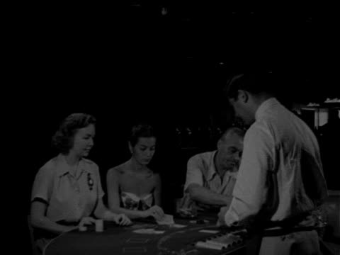 angled ws two females amp male sitting at table w/ male dealer woman gesturing w/ cards for 'hit' dealer giving third card hand 'over' dealer taking... - blackjack stock videos and b-roll footage