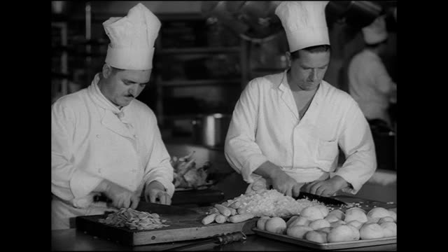 vidéos et rushes de hd angled ms two male sous chefs cutting vegetables one chopping carrots other dicing onions soft kitchen activity bg preparing commercial... - 1949