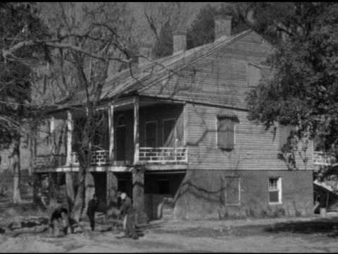 angled two story brick & clapboard two house w/ second floor porch & partial banisters, african-american men in sweater, jackets shoveling dirt w/... - brick house stock videos & royalty-free footage