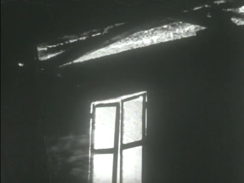 night angled ws two story house burning inside fire flames behind windows doorway roof arch soldiers in silhouette moving outside day ha angled ws... - 1938 stock-videos und b-roll-filmmaterial