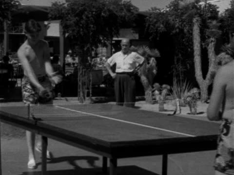 Angled WS Two teenage males dressed in shorts no shirts playing ping pong on table outdoors w/ senior male watching Game paddles ball net amateur...