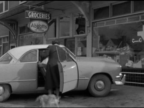 angled ws two women lifting two children into front seat of parked 1951 ford twodoor sedan car cocker spaniel family dog jumping into back seat woman... - ford motor company stock videos and b-roll footage