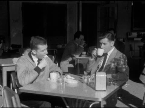 angled ws two young adult male customers sitting at sunny outdoor table w/ coffee cups eating beignets drinking from cups one w/ cigarette waiters... - diner stock videos & royalty-free footage