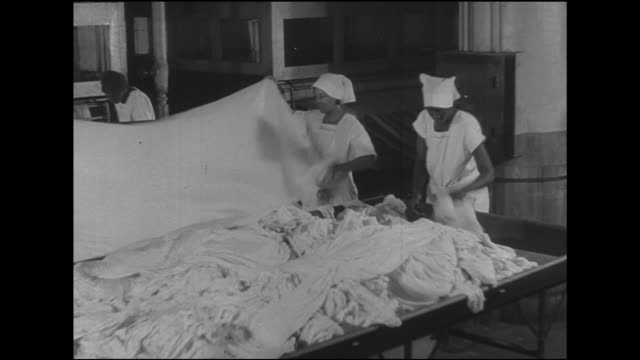 Angled WS Two young adult women workers taking sheets out of bin stretching length laying sheet flat over ironing machine ledge two other women BG...