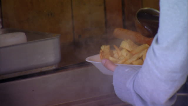 angled ms unidentifiable female hand behind counter holding dish of sausage chips pouring brown gravy over top carrying dish toward sunny counter - brühe stock-videos und b-roll-filmmaterial