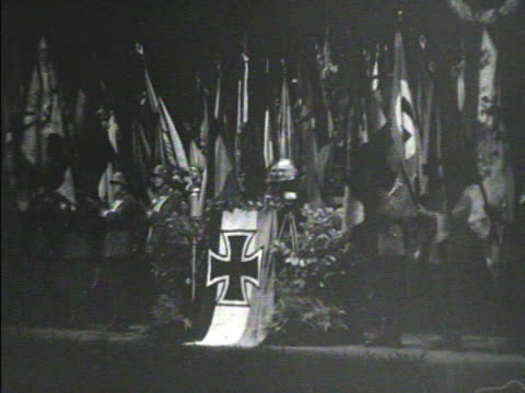 vidéos et rushes de changes angled ws unidentified man at podium w/ wwi iron cross banner soldiers bg w/ flags on poles tilting flags forward mot 1934 waiting hd ms male... - 1934