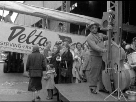 Angled WS Upright bass player of Dixieland band playing on platform w/ Delta Steamship Line cruise ship port ramp waiting people BG woman taking...
