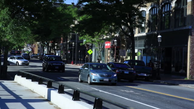 angled ms vehicles driving up down central street unidentified male riding skateboard buildings w/ storefronts - lowell stock videos & royalty-free footage