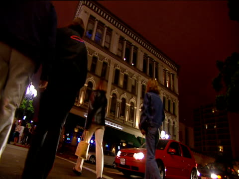 angled view as pedestrians cross road in front of awaiting traffic at night edwardian style building in background san diego - san diego stock videos and b-roll footage
