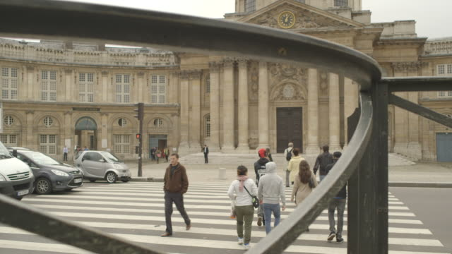 Angled view of a group of people crossing a level crossing outside the Institut de France, Paris.