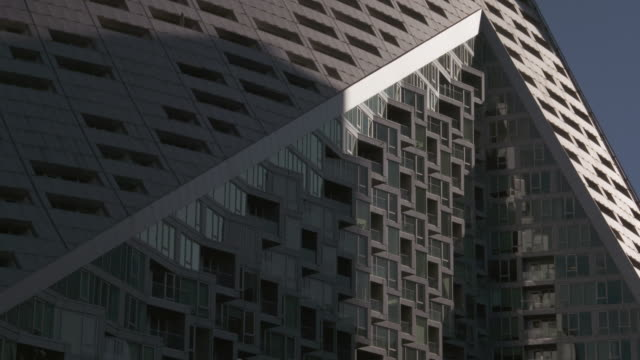 Angled windows and balconies of uniquely designed New York City building sits half in the sun.