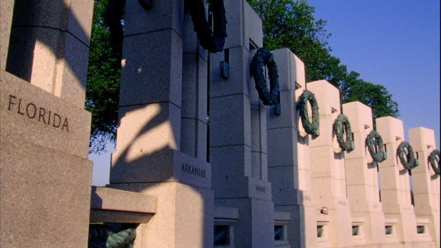 Angled WS World War II Memorial pillars w/ bronze sculptured wreaths blue shadows sunlight Florida Arkansas Maine