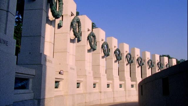 Angled WS World War II Memorial pillars w/ bronze sculptured wreaths blue shadows sunlight Maine