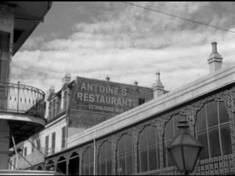 angled xws 'antoine's restaurant' sign painted on upper section of rue saint louis building side wall partial curved gallery ornate ironwork around... - saint louis bildbanksvideor och videomaterial från bakom kulisserna