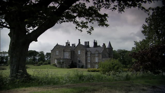 angled xws back of menie house mansion & landscaped grounds, strong wind, menie house. 14th century, retreat, stone, haunted, green lady ghost,... - scotland stock videos & royalty-free footage