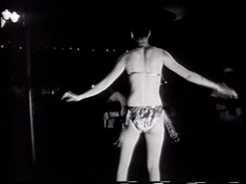 vídeos de stock, filmes e b-roll de olongapo philippines night angled ws 'zanzibar' sign on building w/ three lighted stories vs filipino exotic dancer dressed in fringed bikini dancing... - stripper