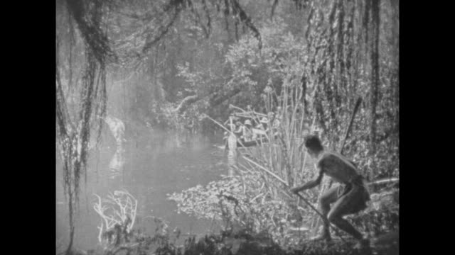 stockvideo's en b-roll-footage met 1925 anglo explorers in boats startle native man with spears in jungle - inheemse cultuur