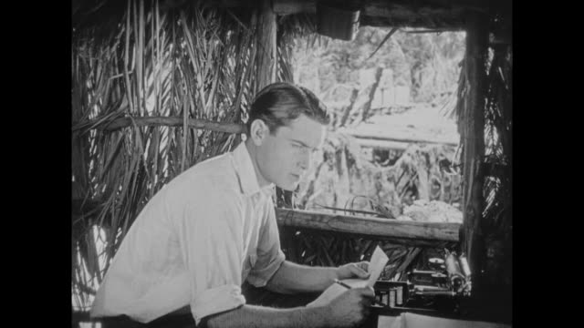 1925 anglo man sits typing love letter in grass hut - 1925 stock videos & royalty-free footage