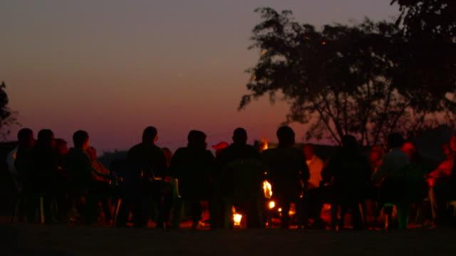 Angolan men sit around bonfire at sunset