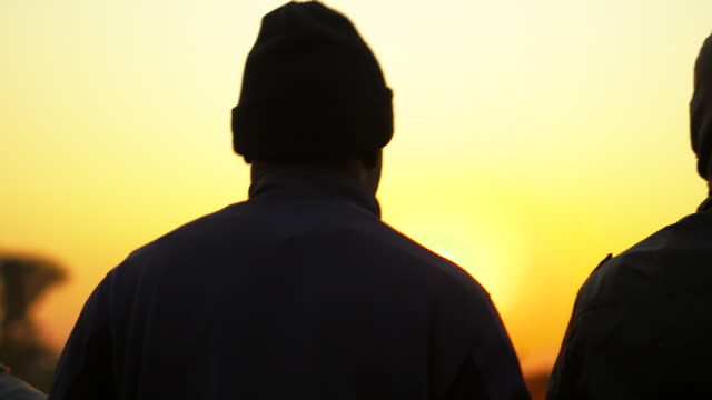 Angolan men walk during sunset