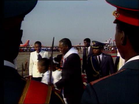 Angolan president Dos Santos along at airport Dos Santos in back of car waving to crowds LIB Jonas Savimbi casting vote in election