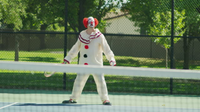 angry aggressive clown playing tennis / pleasant grove, utah, united states - tennis stock-videos und b-roll-filmmaterial
