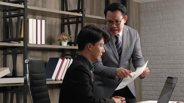 wütender asiatischer chef ärgert sich über mitarbeiter wegen arbeitsfehler im büro - aggression stock-videos und b-roll-filmmaterial