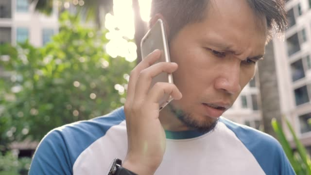 Angry asian man talking on the phone.Upset depressed businessman