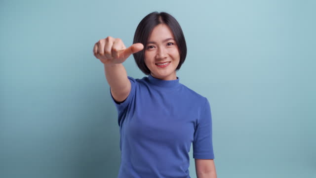 angry asian woman looking at camera and show thumb up to down standing isolated on blue background. 4k video - stop sign stock videos & royalty-free footage