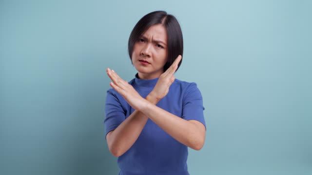 青い背景に孤立したカメラを見ている怒っているアジアの女性。4kビデオ - 身ぶり点の映像素材/bロール
