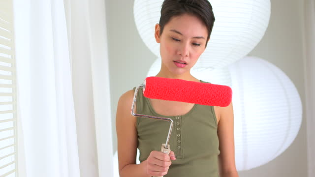 angry asian woman with paint roller in hand - distraught stock videos & royalty-free footage