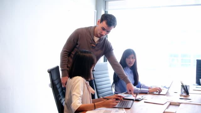 Wütend Chef Schelte Arbeitnehmerin für schlechte Arbeitsergebnis am Konferenztisch, männliche Direktor inkompetent untergeordnet die Schuld für Fehler im Finanzdokument bei diversen Teambesprechung anzuschreien.
