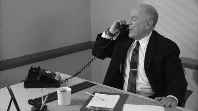 b/w ms angry businessman hanging up phone in office/ man resting head in hands and looking stressed/ new york city - hanging up stock videos and b-roll footage