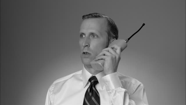 b/w cu angry businessman having conversation on large  early mobile phone/ new york city - sladdlös telefon bildbanksvideor och videomaterial från bakom kulisserna