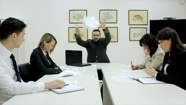 Angry businessman shouting and throws papers at his workers with an expressive look