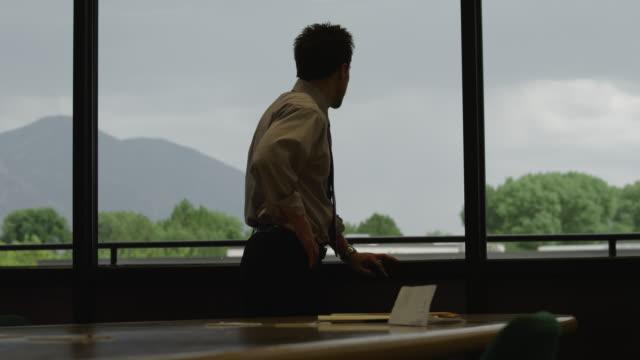 vídeos y material grabado en eventos de stock de ms zo angry businessman standing at window in conference room / orem, utah, usa - puño gesticular