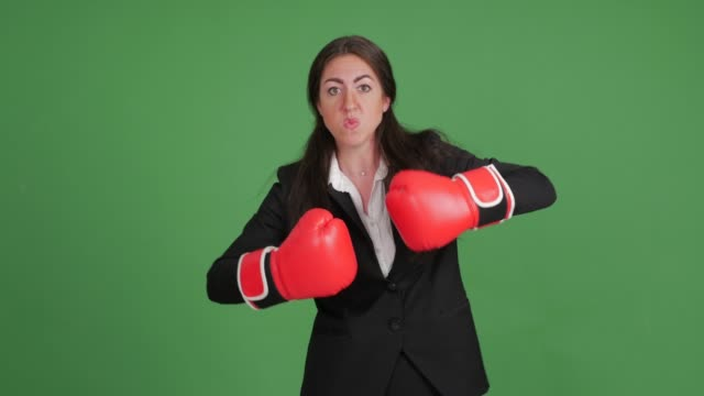 angry businesswoman in boxing gloves on a green background