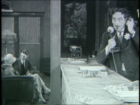b/w 1925 angry desk clerk in hotel hanging up telephone / silent film - 1925年点の映像素材/bロール