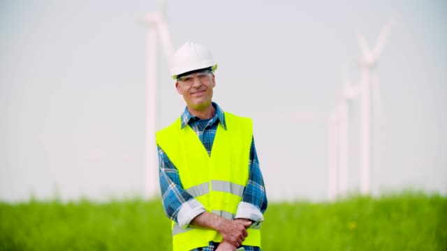 Angry Engineer Talking On Mobile Phone against Windmills Farm