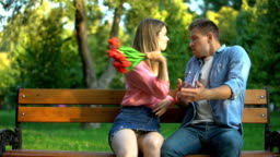 Angry girl hitting boyfriend with bunch of tulips, unsuccessful apology, quarrel