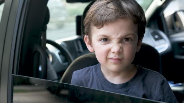 wütender kleiner junge, der seine gesichtsmaske entfernt und durch ein autofenster in die kamera schaut - displeased stock-videos und b-roll-filmmaterial
