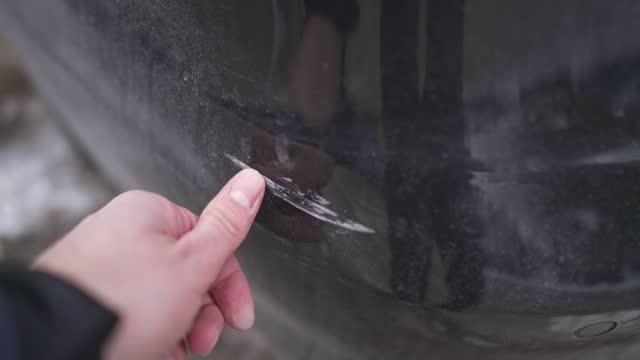 arg man undersöker med fingret en bil repa efter att han hade en bilolycka - repad bildbanksvideor och videomaterial från bakom kulisserna