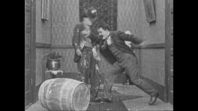 vídeos de stock, filmes e b-roll de 1915 angry man runs upstairs and starts fighting with charlie chaplin and pushes him to the ground - charlie chaplin