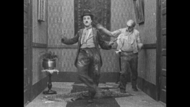 vídeos de stock, filmes e b-roll de 1915 angry man runs upstairs, starts fighting with charlie chaplin and a shooting gun haphazardly at everyone in house as he runs around - charlie chaplin