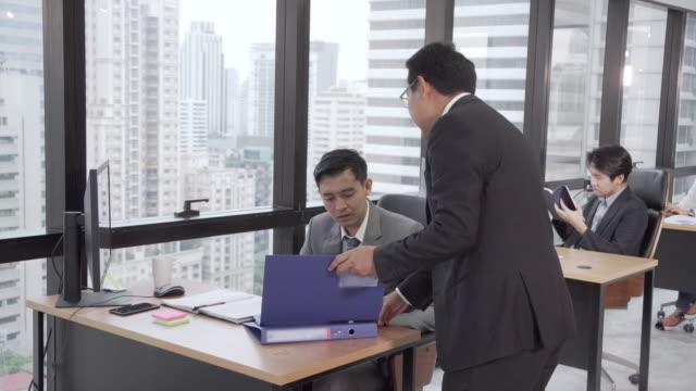 ネクタイとスーツを着て怒っているマネージャーは、高層オフィスでデスクトップコンピュータと彼の机の上に座ってビジネスマンに不平を与える。 - 疑念点の映像素材/bロール
